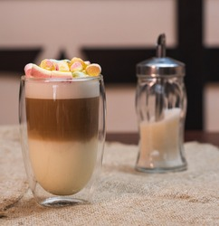 Delicious freshly made coffee latte with marshmallows stands on the table