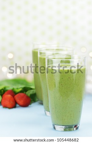 Delicious freshly made Spinach and Strawberry smoothies made with cold milk, yogurt, spinach and strawberries. Extreme shallow depth of field with selective focus on glass in foreground.