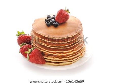 Delicious freshly prepared pancakes with strawberry and blueberries isolated on white