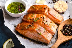 Delicious fried salmon fillet, seasonings on blue rustic concrete table. Cooked salmon steak with pepper, herbs, lemon, garlic, olive oil, spoon. Grilled fresh fish. Fish for healthy dinner. Close-up