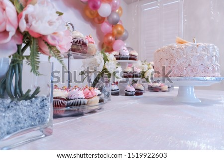 Delicious Frosted Cupcakes, Frosted Cake, and Flowers on top of a Beautiful White Table #1519922603