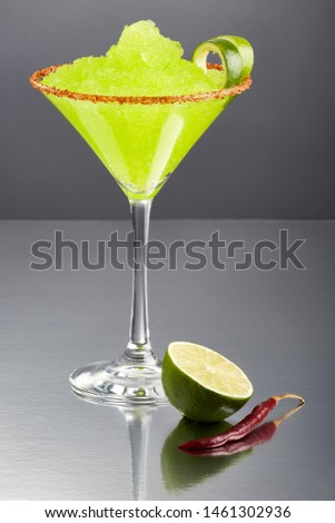 Delicious frozen lime Margarita cocktail rimmed with salt and bird's beak chile or chili pepper and a twist of lime by a half of a lime and a full dry bird's beak chile, on a grey background