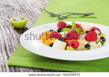 delicious fruit  and berry summer salad decorated with mint leaves in white wide rim dish on wooden boards, close up