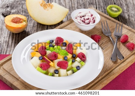 delicious fruit  and berry summer salad decorated with mint leaves in white wide rim dish on wooden boards, view from above, selective focus