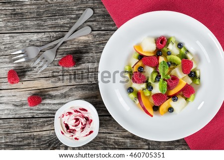 delicious fruit  and berry summer salad decorated with mint leaves in white wide rim dish with dessert forks on wooden boards and cream sauce bilberry dip, view from above