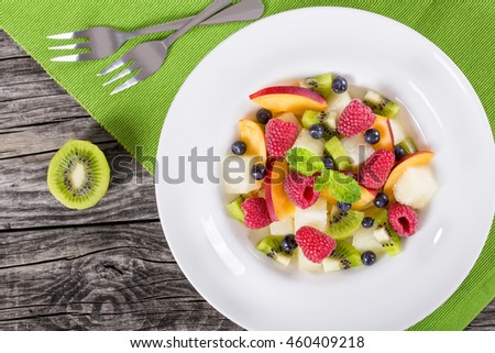 delicious fruit  and berry summer salad decorated with mint leaves on bowl with dessert forks on rustic wooden boards, view from above