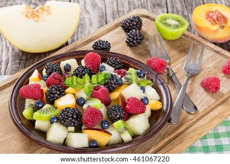 delicious fruit and berry summer salad decorated with mint leaves on clay dish on cutting board with dessert forks, half of peach and slice of melon on rustic boards,selective focus