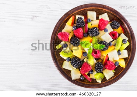 delicious fruit  and berry summer salad decorated with mint leaves on clay dish on white worktop, view from above