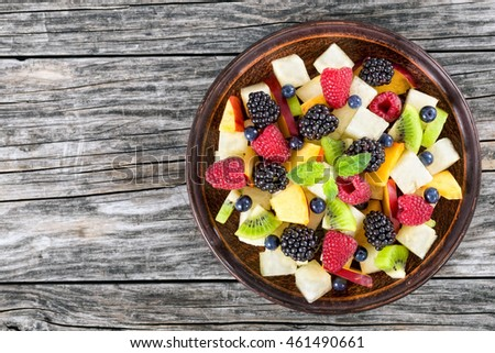 delicious fruit  and berry summer salad decorated with mint leaves on clay dish on wooden boards, view from above, blank space left
