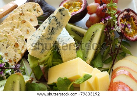 Delicious fruit and cheese platter featuring a variety of different cheeses and fresh fruits.