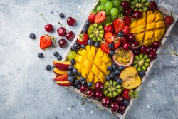 delicious fruits and berries platter.  Mango, kiwi, strawberry, grape, cherry, blueberry, peach and passion fruit on wooden tray, top view, copy space