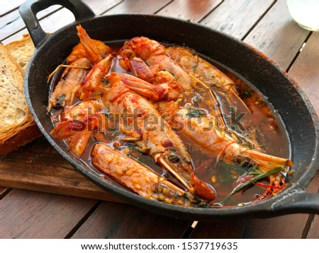 Delicious Gambas pil pil in hot garlic oil and chilli in Marbella Spain, traditional Spanish dish with prawns, garlic and chilli with toasted bread on the side in a black pan in Costa del Sol Foto d'archivio ©