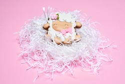 Delicious gingerbread in shape of cute sheep covered with tasty glaze for Easter. One colored biscuits in decorative net isolated over pink background.