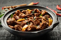 Delicious goat meat curry served in a clay cookware .