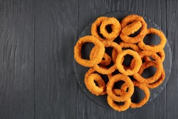 delicious golden battered, breaded and deep fried crispy onion rings served on round black stone tray on black wooden table, view from above, close-up