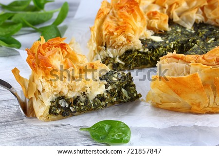 delicious golden crust hot greek spinach feta cheese pie or spanakopita cut in slices on white paper with spatula on table, authentic recipe, side view from above, close-up