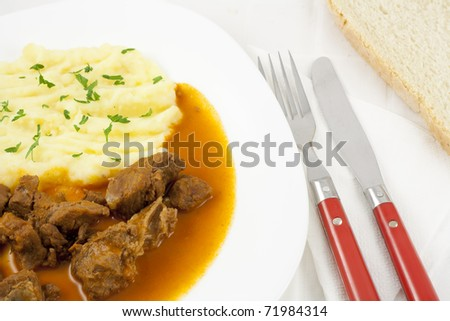 Delicious goulash with mashed potato spiced with parsley and slice of bread.