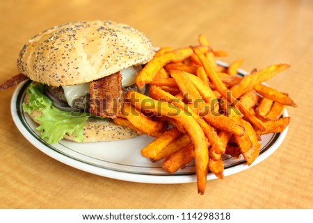 Delicious gourmet hamburger served with sweet potato French fries at a restaurant.