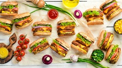 Delicious grilled burger with beef, tomatoes, cheese and lettuce on a white wooden background. Top view with copy space. The concept of fast food and junk food