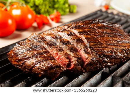 Delicious grilled meat over the grill on a barbecue #1365268220