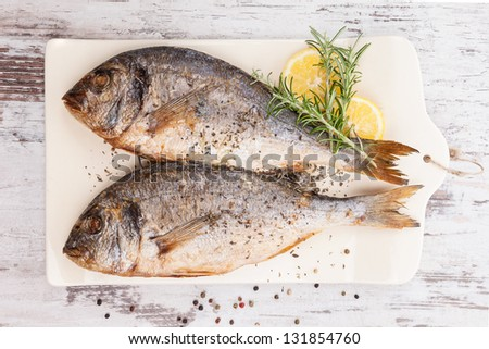 Delicious grilled sea bream fish on kitchen board with rosemary, lemon and colorful peppercorns on white textured wooden background. Culinary healthy cooking.