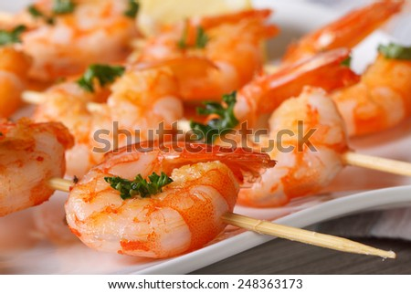 Delicious grilled shrimp on wooden skewers on a plate macro. horizontal
