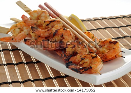 Delicious grilled shrimp served with lemon wedges. - stock photo
