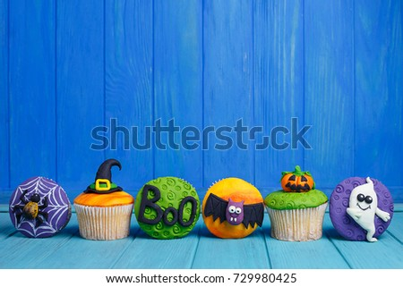 Delicious Halloween cupcakes set with bright decorations made of confectionery mastic. Halloween sweets, homemade confectionery, holiday food, trick or treat concept
