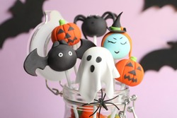 Delicious Halloween themed cake pops on pink background, closeup
