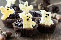 Delicious Halloween treat for dessert, chocolate muffins with  sweet white chocolate ghosts