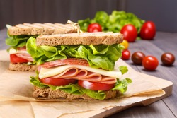 Delicious Ham, Salami, Cheese and Vegetables Sandwiches on Toasted Whole Grain Bread Isolated on white