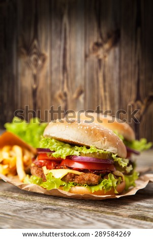 Delicious hamburger and french fries on wooden background