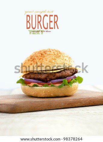 Delicious hamburger isolated on white with copyspace. Burger on wooden board - stock photo