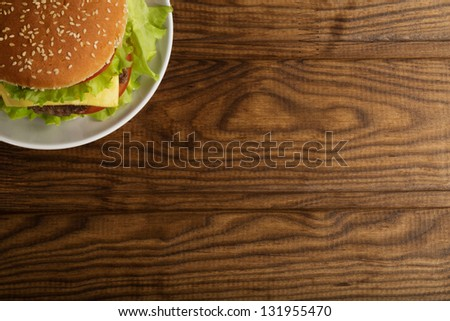 Delicious hamburger stacked high with a juicy beef patty cheese fresh lettuce onion and tomato on a fresh bun with sesame seed standing on wooden table