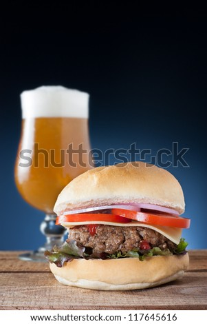 Delicious hamburger with cheese, onion, tomato and lettuce served with a beer