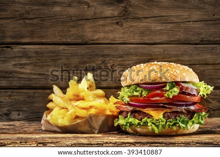 Delicious hamburger with french fries on wooden table