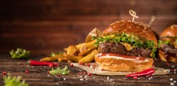 Delicious hamburger with fries, served on wood. Free space for text