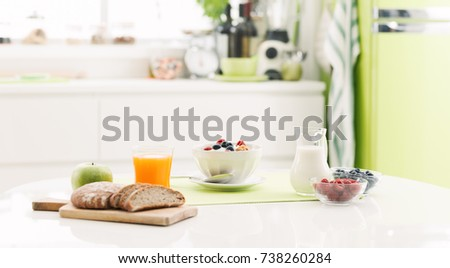 Delicious healthy breakfast at home with cereals, milk and fresh fruit; kitchen interior on the background