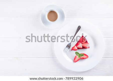 Stock Photo Delicious healthy vegetarian food, no bake organic strawberry cheesecake slices, fresh red berries, green mint leaves, cup of coffee, fork. white wood texture table. Close up, top front view.