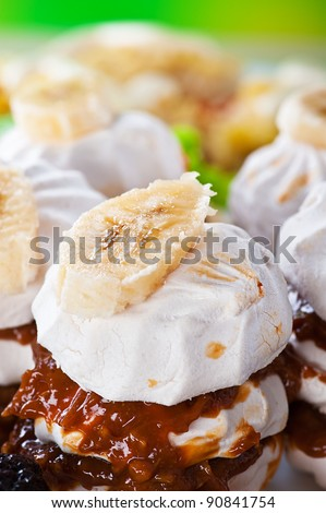 delicious holiday dessert meringue, marshmallow, whipped cream, condensed milk is decorated with slice of banana on a green background