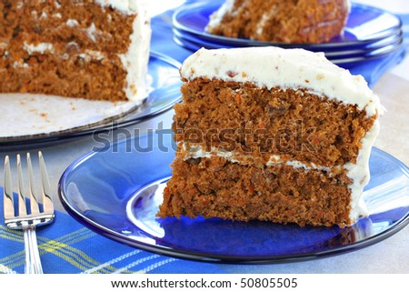 Delicious homemade carrot cake with cream cheese nut frosting.  Sliced on blue glass plates with cut cake in background.