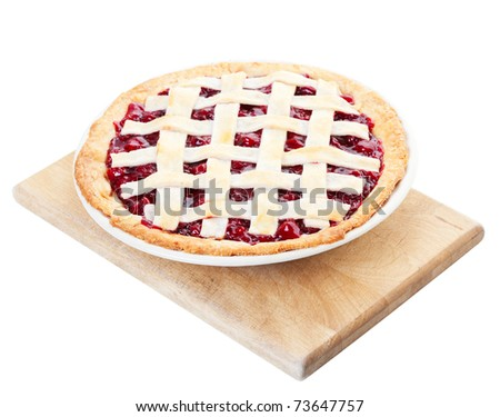 Delicious homemade cherry pie cooling on a wooden cutting board. Shot on white background.