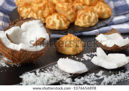 delicious homemade coconut macaroons cookies on a stone plate on a black wooden table with ingredients at foreground, horizontal view from above, close-up