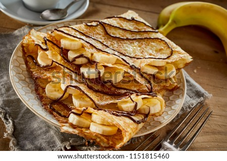 Delicious homemade golden fried banana pancakes with castor sugar drizzled with chocolate sauce served for a wholesome country breakfast on a rustic table