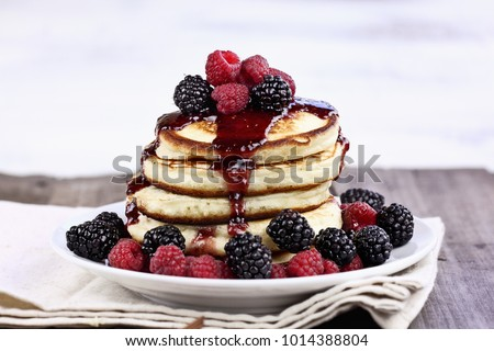 Delicious homemade golden pancakes with fresh blackberries, raspberries, and raspberry syrup. Extreme shallow depth of field.