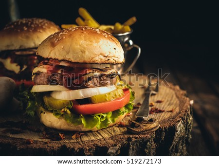 Delicious homemade hamburger with lettuce and cheese. Fried chips and burger on wooden background. VIntage toned.