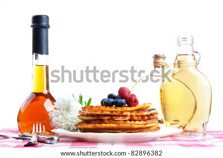 Delicious homemade pancakes with maple syrup and forest fruits, still life.