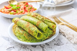 Delicious homemade ramson pancakes or crepes with tomato salad on white background