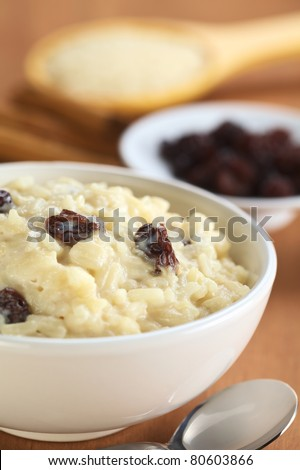 Delicious homemade rice pudding with raisins; with raisins, cinnamon sticks and raw rice on wooden spoon in the back (Selective Focus, Focus on the two raisins in the middle of the bowl)