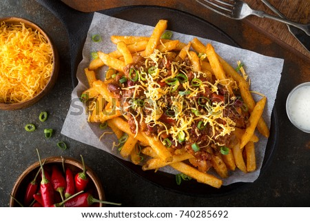 Delicious homemade spicy chili fries with green onion and cheddar cheese.